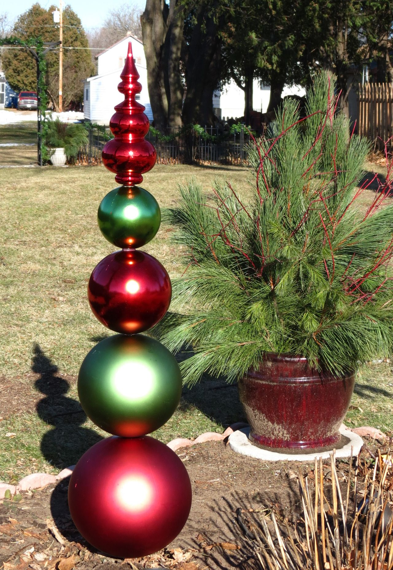 a christmas totem for the yard made from plastic ornaments art