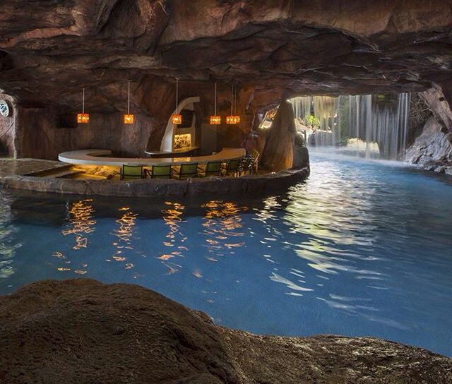 Bar in a pool grotto behind a waterfall home ideas for Swimming pool grotto design
