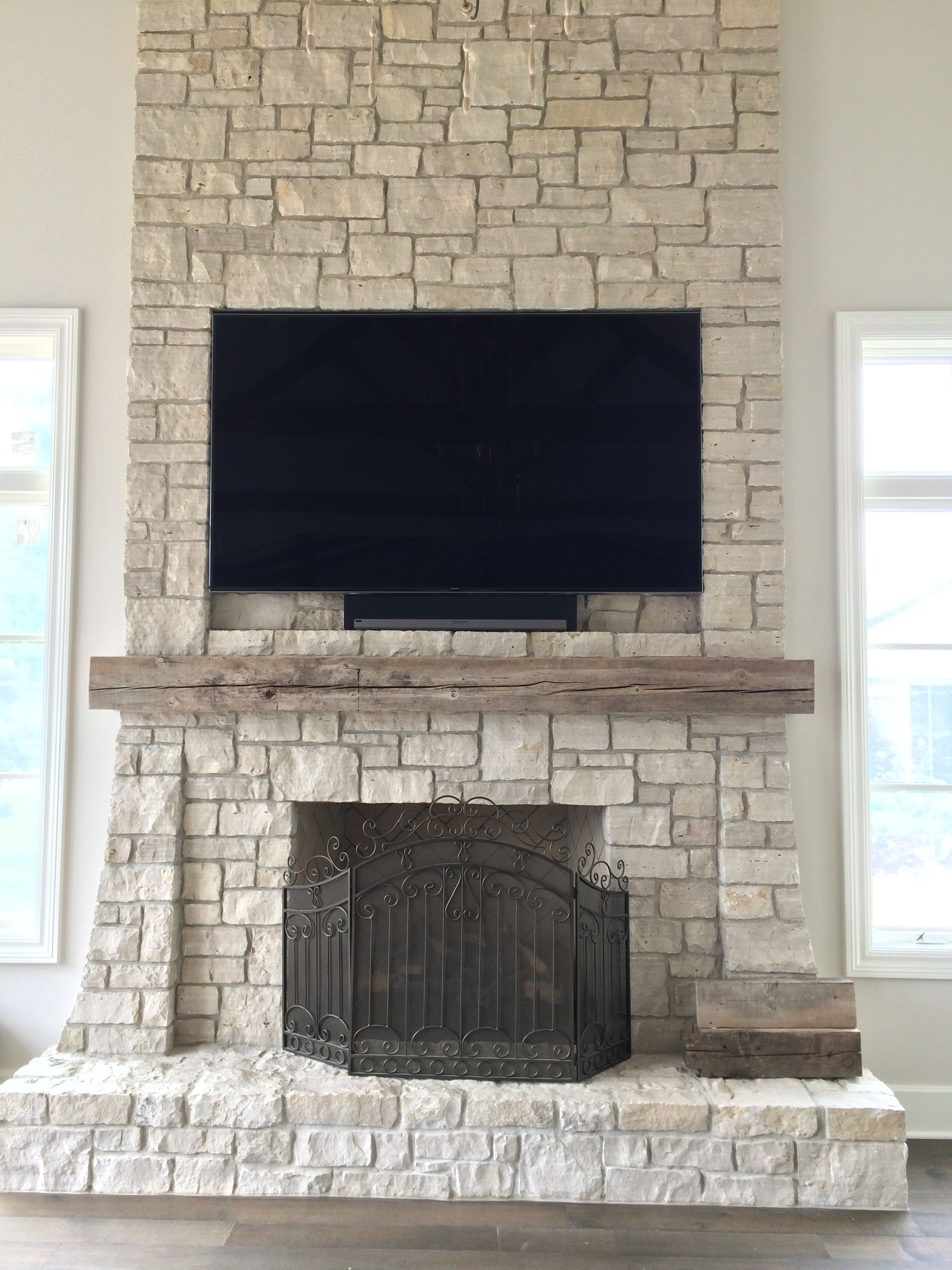 Flat Panel Tv Mounted And Inset Into Stone Facade Over A Fireplace With Sonos Playbar Seamlessly Beneath