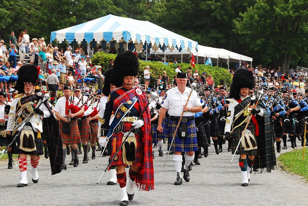A parade of pipers circles the field at the Grandfather