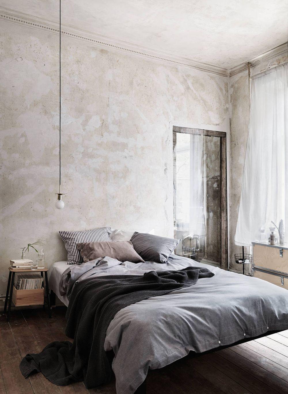 Un mur marqué par le temps et du linge de lit taupe et gris pour une chambre cocooning
