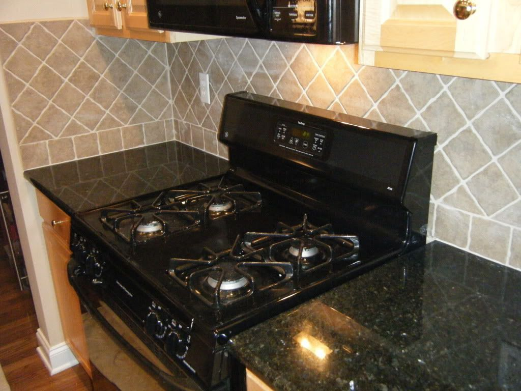 Kitchen black granite tile countertop and electric stove set on black granite tile countertop and electric stove set on grey backsplash wall dailygadgetfo Images