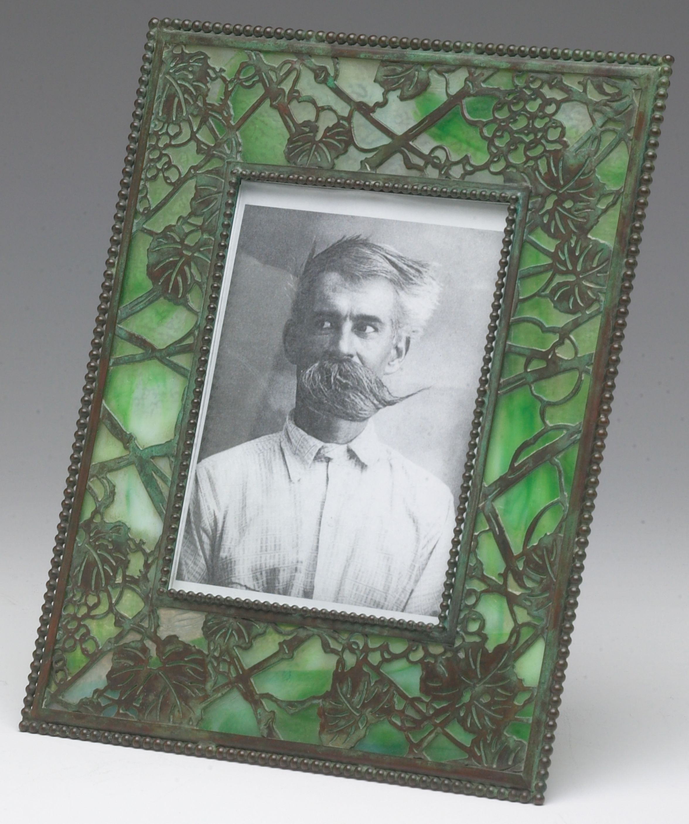 A tiffany studios new york grapevine pattern picture frame circa a tiffany studios new york grapevine pattern picture frame circa 1900 a patinated bronze tiffany studios new york etched metal glass picture frame in jeuxipadfo Image collections