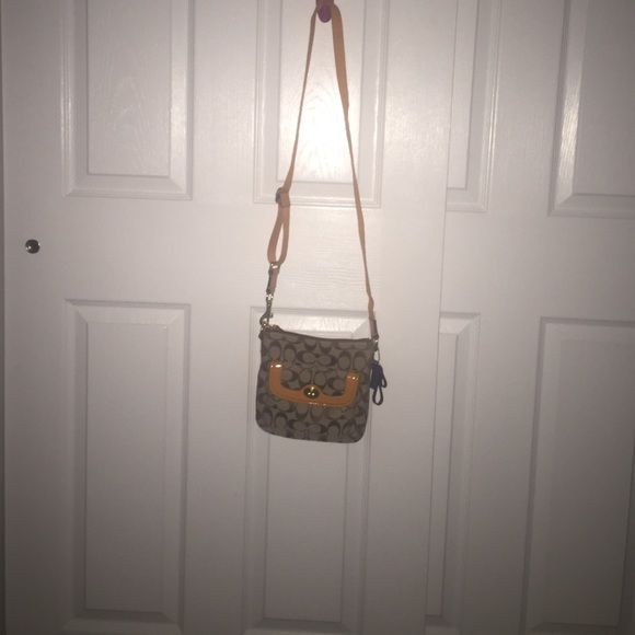 A coach sling/ cross body purse It's tan with orange detailing and blur zippers and it's brand new and was never used (got as a gift but never used) Coach Bags Crossbody Bags