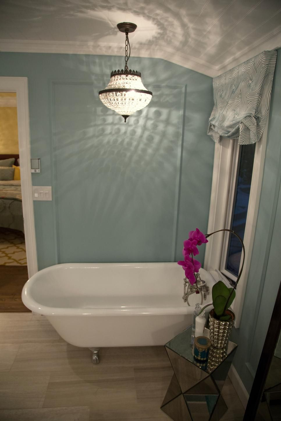 A dazzling chandelier hangs above a clawfoot tub in this light blue