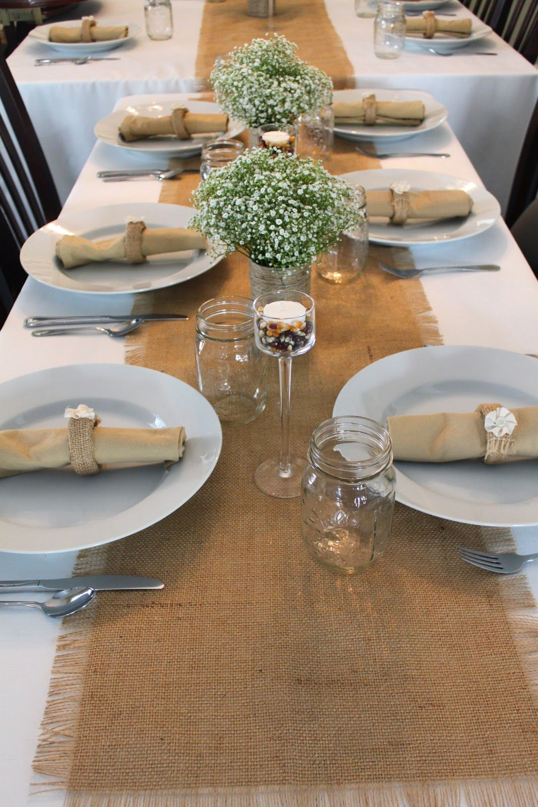 Lovely centerpieces and the burlap looks great on the white tablecloth. Replace the beige napkins & Lovely centerpieces and the burlap looks great on the white ...