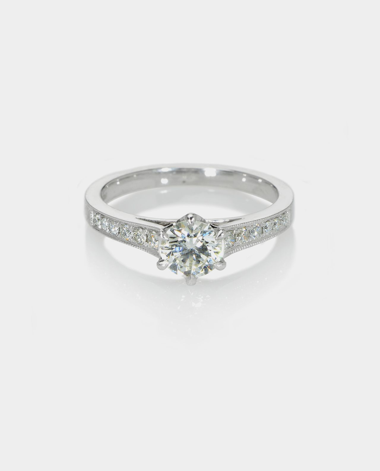 18ct white gold single stone diamond ring with bead-set shoulders.
