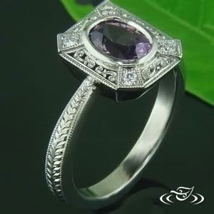 Custom cast palladium mounting with .93ct purple sapphire center stone set in a full bezel. Emerald cut halo with raised diamonds on four corners and engraving in between. Band has a reverse taper with full wheat engraving going down the sides.