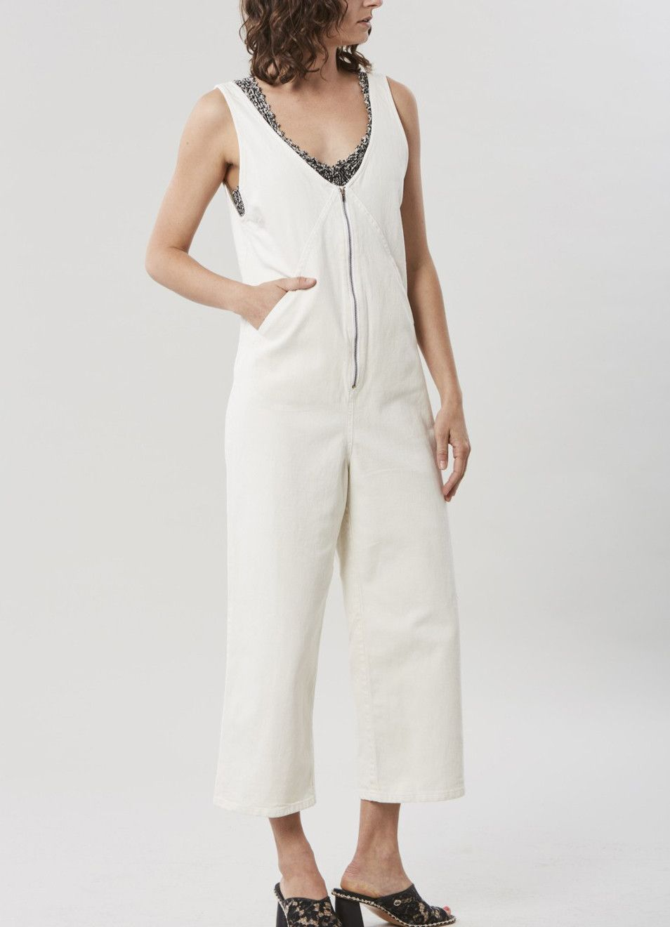 9f6580aaa49a Sleeveless jumpsuit in our Dirty White denim with deep v-neck. Exposed  front zip closure and slit pockets at the hip. Wide