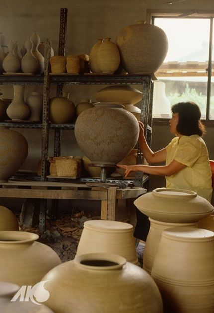 eastasianstudiestumbl:  Korean ceramic workshop. You can see the woman working on the incised decoration.