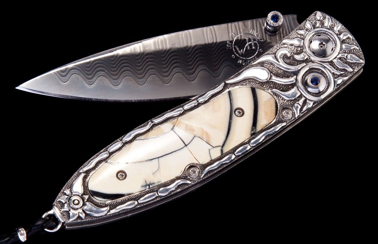 William Henry's Monarch 'Starburst' features a beautiful frame in hand-carved sterling silver, inlaid with a mesmerizing scale made from the ring-cut fossil tusk of a Woolly Mammoth that lived 10,000 years ago. The blade is in black-coated 'wave' damascus steel with an extra strong core in ZDP-189. The one-hand button lock and the thumb stud are set with sapphire.