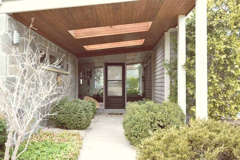 Butterfly house deeply recessed entry with skylights built in planters big sidelight windows flanking the front door