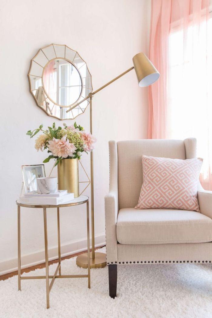 amenagement coin de lecture avec fauteuil beige et coussin rose et blanc modele de table en verre et cuivre