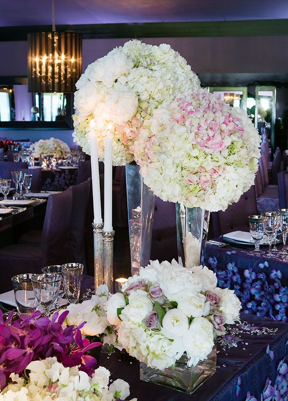 Pomanders Of Peonies And Hydrangeas Rest Atop Tall Silver Trumpet Vases For Chic Wedding Centerpieces
