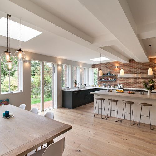 Love all the windows, sleek range hood, no uppers, both black and white cabinetry and wood floors #darkflooring