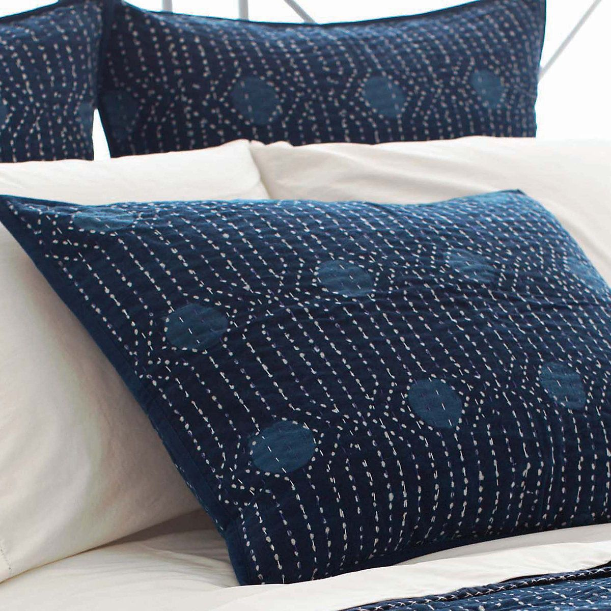 Inspired by traditional Indian kantha quilts, this cotton pillow features a block-style print on an ink-colored background and a contrast running stitch on top.