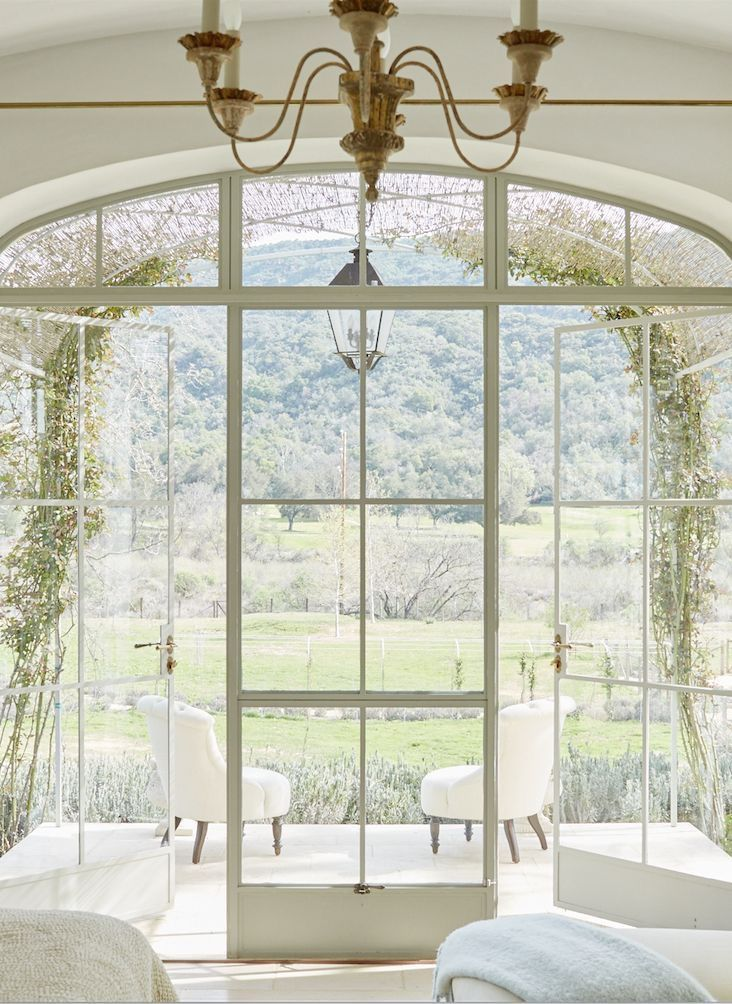 French country and French farmhouse interior design inspiration from a modern farmhouse (Patina Farm). Dreamy serenity of an arched steel trellis embraced with reed vine fencing. #frenchfarmhouse #frenchcountry #archedwindow #interiordesign #modernfarmhouse #romantic