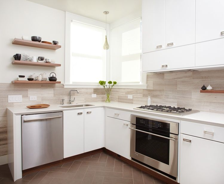 Floor Tile In Herringbone Pattern, Wood Kick Plate Contrasting With  Cabinets, Backsplash Tile, And Daylight Flooding The Space