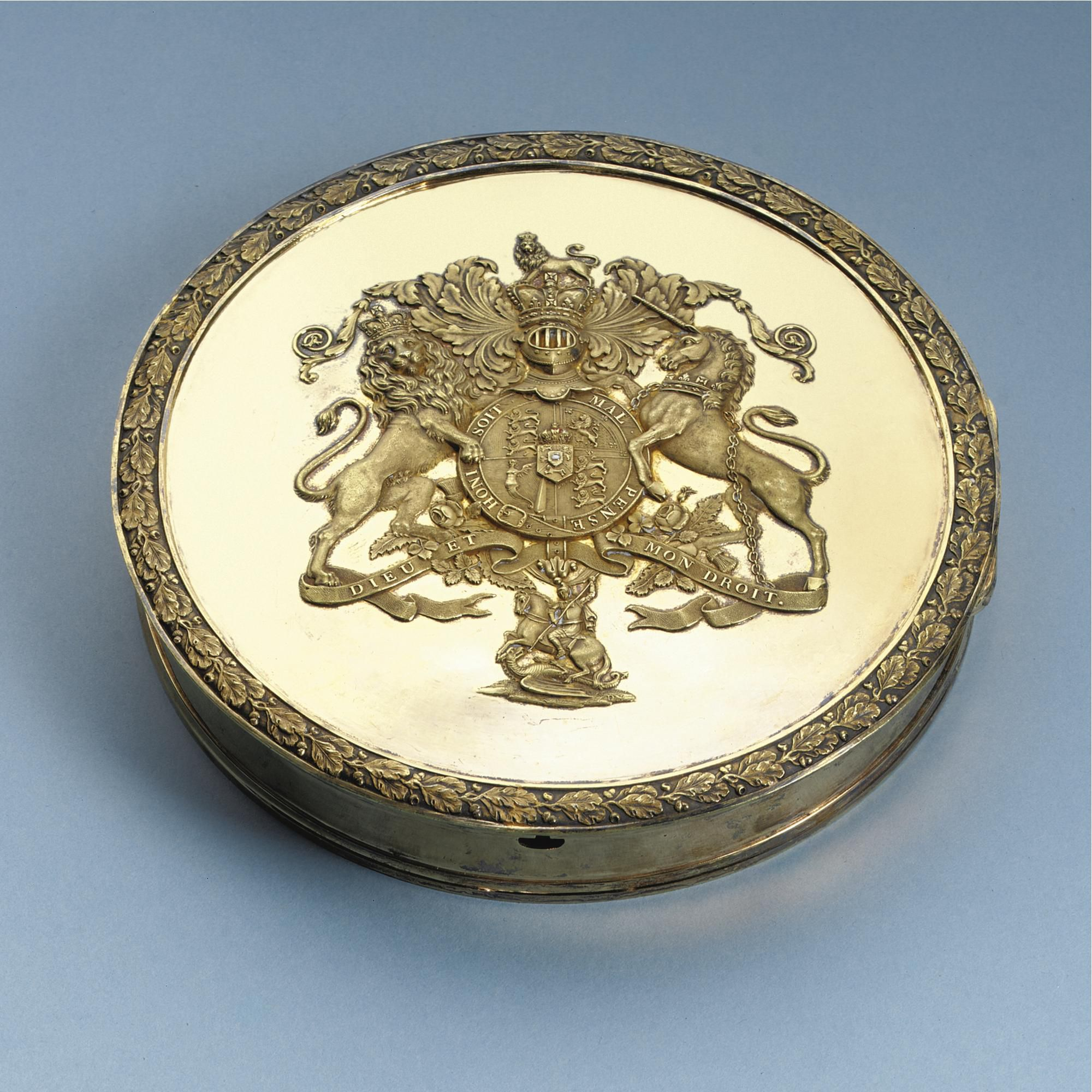 A Regency Royal Silver-gilt Seal Box, Paul Storr, London, 1817 of shallow drom form, the hinged cover embossed with the Royal Arms within a border of running oak leaves and acorns, marked on base and cover diameter 6 3/4in.
