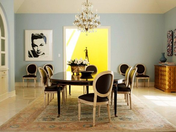 Blue dining room with faded Persian rug, black leather dining chairs, and chandelier.