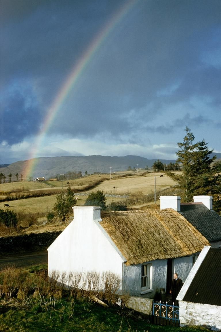 Picture of a rainbow over a thatched white cottage in Ireland