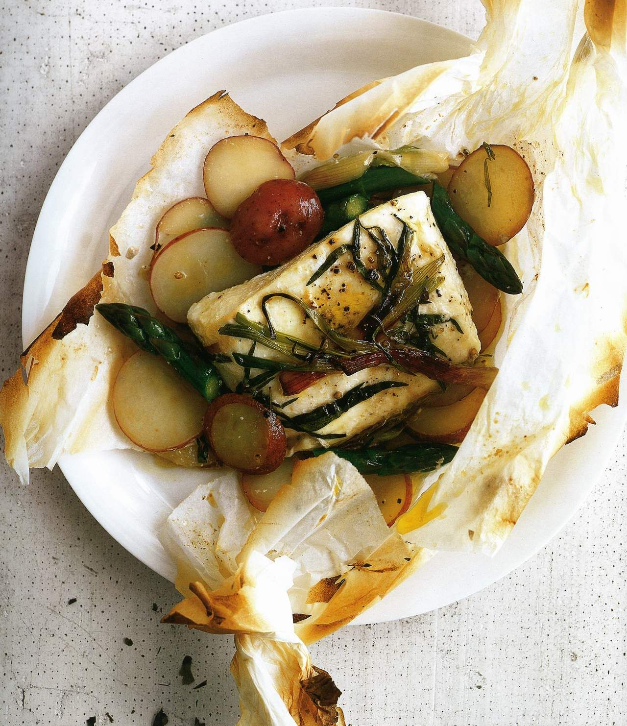 halibut in parchment paper You will need a 14 x 12 inch piece of parchment paper for each portion of halibut fold in half, making a crease down the middle using kitchen shears, cut the parchment into a heart shape.