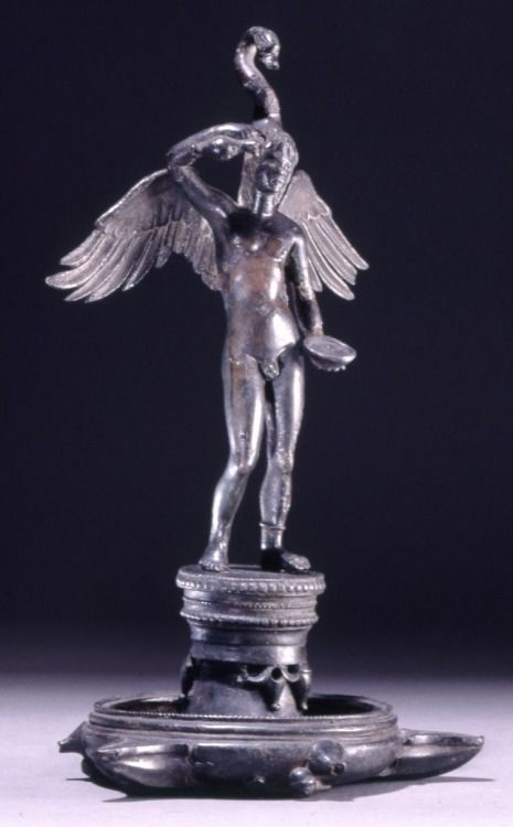 Bronze three-nozzled hanging lamp surmounted by a statuette on a plinth 300-200 BC Etruscan This winged figure wears a swan's head cap and appears to be an Etruscan spirit connected with the rural and Dionysiac world, and links with the scene on the underside of the lamp. (Source: The British Museum)