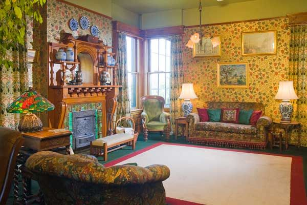 The front end of the drawing room includes an original fireplace and mantel. A leaded window interrupts the chimney