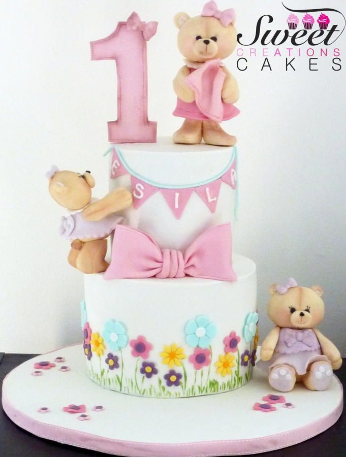 Spring first birthday cake with bears bunting and bows