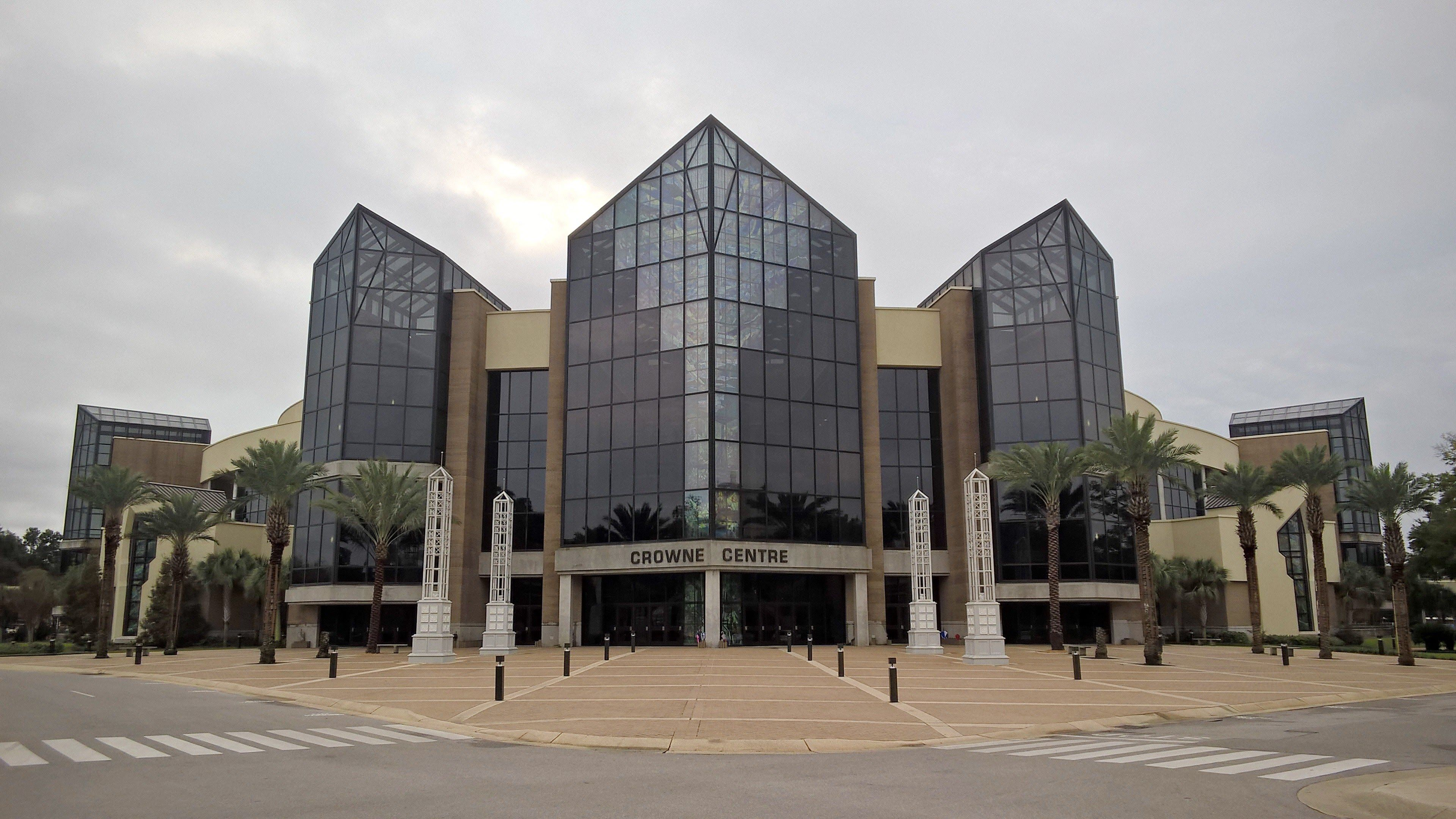 The Crowne Center, home of the Campus Church, is an imposing structure with a main auditorium capacity of over 6000 seats, plus two chapels and other side rooms. The imported palms seen here, too sensitive to freezing, were replaced in the summer of 2016. Stubs from palms toppled by the last hurricane remain visible.