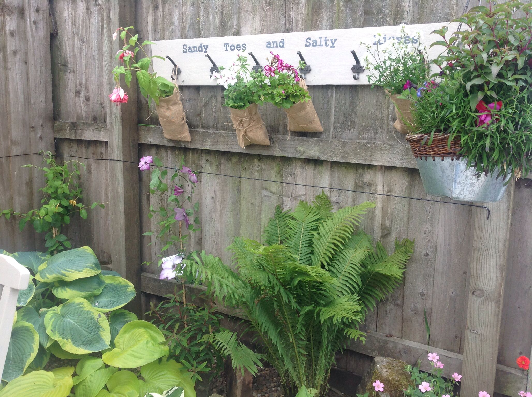 Hanging burlap plant pockets on an old painted plank for Alternative planters