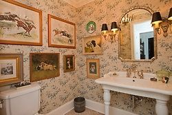 The English penchant for walls filled with framed pictures extends to the bathroom
