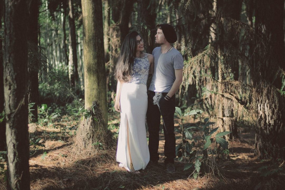 #people  #person  #human #man #and #woman  man and woman standing together surrounded by green trees and plants during daytime Stylish couple in the woods