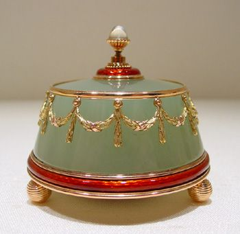 Faberge-A Guilloche enamelled gold mounted carved bowenite body bound a band of scarlet red guilloche enamelled gold and two colored gold festoons, the cabochon moonstone push held in a gold mount similarly enamelled red, supported on three gadrooned spheres bell push.