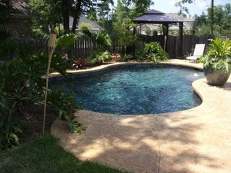 Tropical Design Swimming Pool Backed By Rich Tropical Foliage And A Beautiful Stamped Concrete Pool Deck Before Pool Builders Concrete Pool Pool Construction