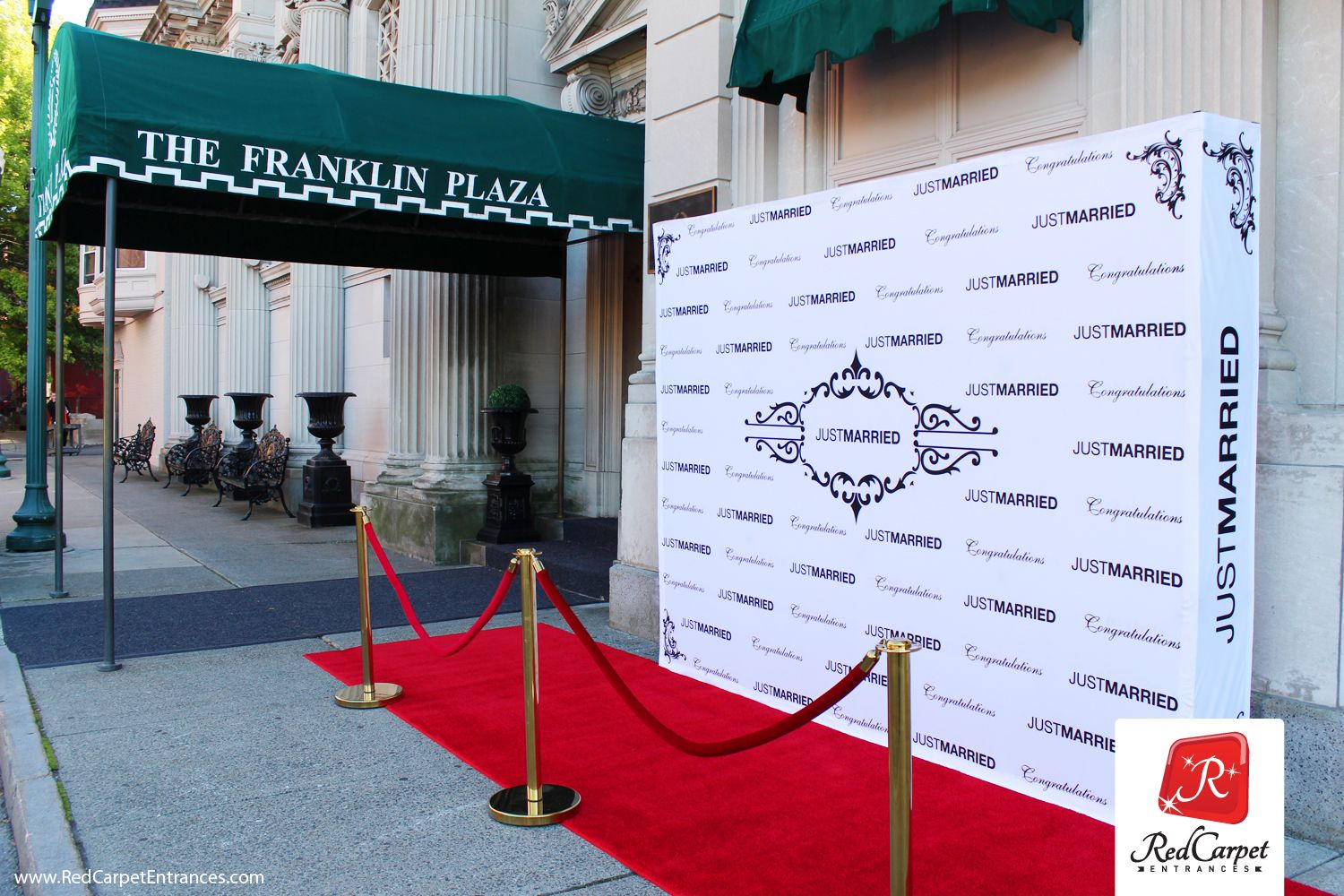 """Red carpet wedding reception entrance at Franklin Plaza in Troy, NY. Plush red runner carpet, """"Just Married"""" fabric step & repeat photo backdrop. Brass stanchions with red velvet velour ropes. Paparazzi photography for guests entering the venue. Red carpet weddings!"""