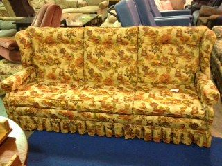 This three seater couch has an old-fashioned fabric design. With a solid  wood