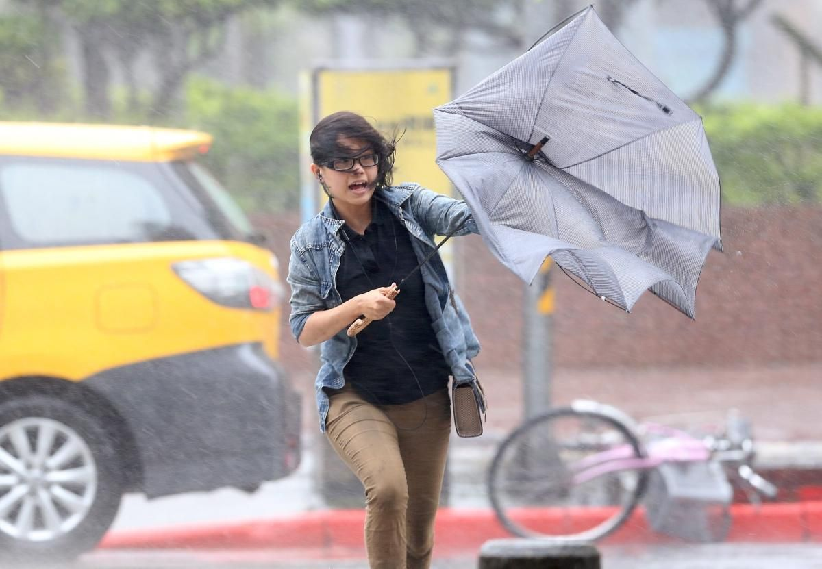 A woman's umbrella is turned inside out by the strong wind in Taipei on July 23, 2014.