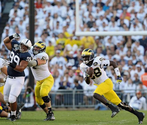 Michigan quarterback Devin Gardener (98) scrambles out of the pocket against Penn State during first half action at Beaver Stadium on Saturd...