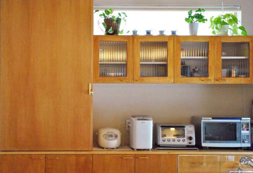 キッチン後ろの収納もすべて造作によるもので「使いやすく実用的」と奥さん。吊り棚にもモールガラスを使用した