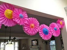 Cinco de Mayo Flower Garland!  Pink plastic tablecloth covering made into pleated flowers with paper umbrellas for the centers!