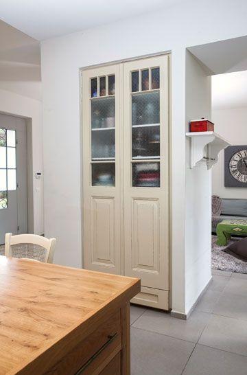 ארון מזווה שנסגר בשתי דלתות ישנות ששופצו. בין המטבח לחדר המשפחה יש ...