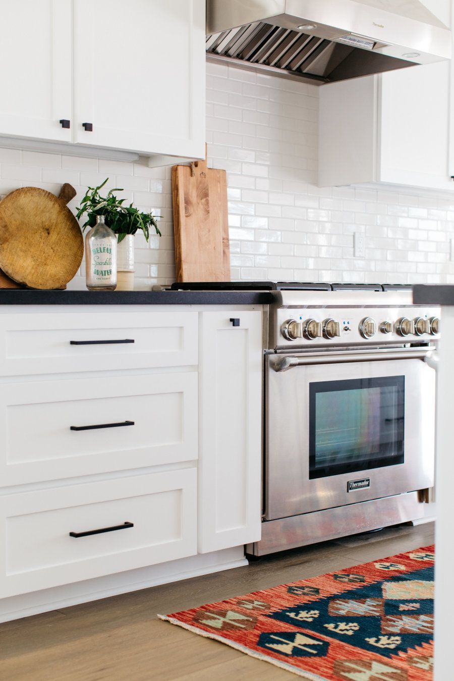 White kitchen with black countertops and a vintage runner