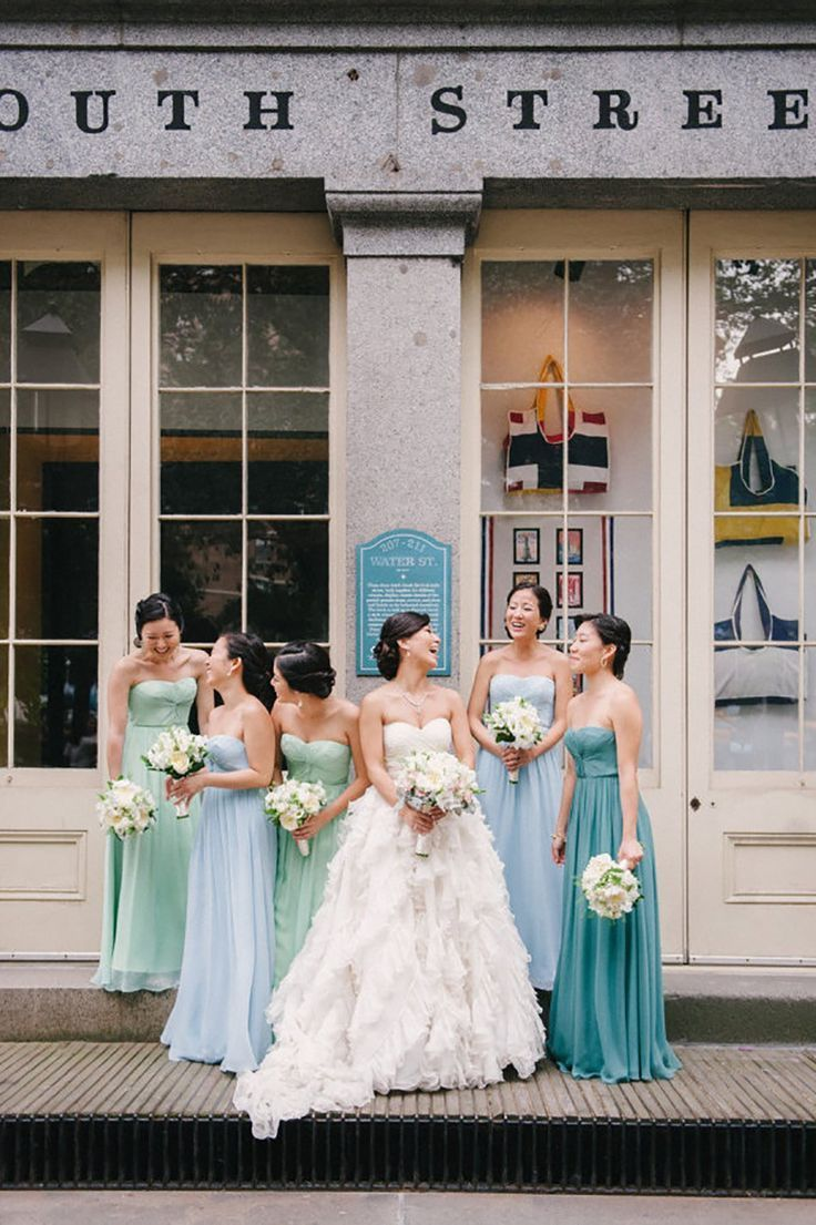 Bride with bridesmaids wearing different coloured blue