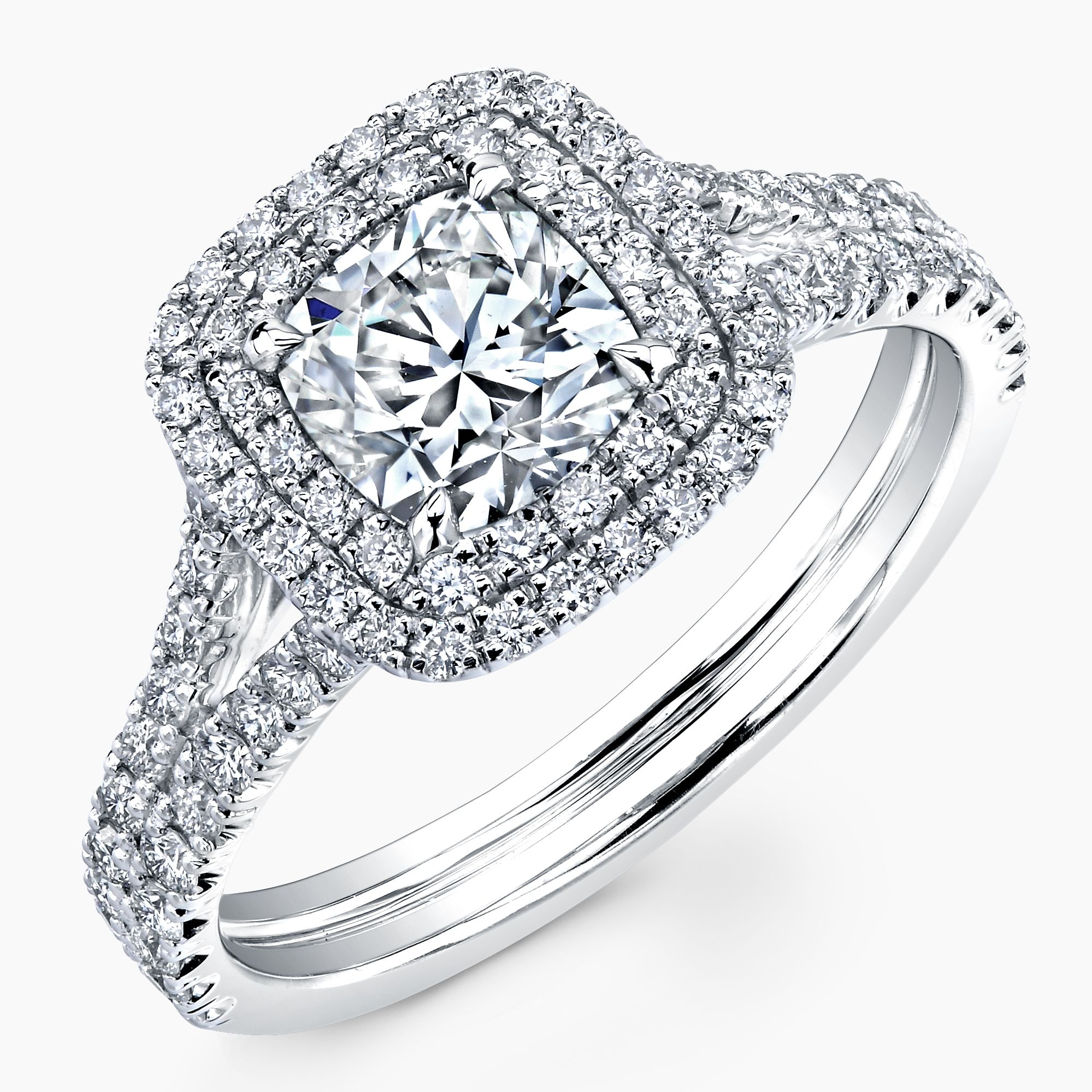 Cushion cut diamond set in 18k white gold split shank with double halo pave r