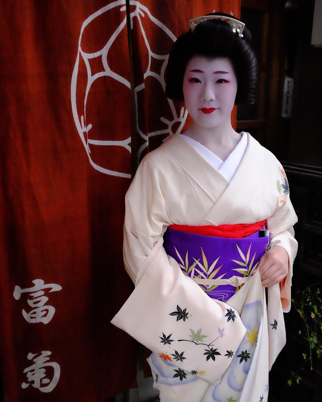 geiko Tomitae standing outside her okiya, by ...