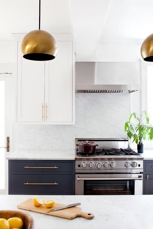 Beside white shaker upper cabinets a stainless steel hood is mounted on a honed cabinets