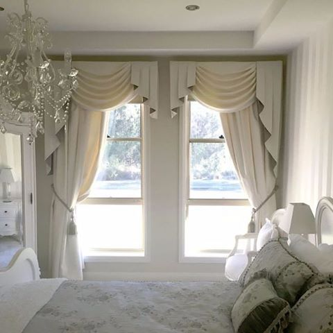 A Beautiful Luxury Bedroom Setting With Decadent Curtains And