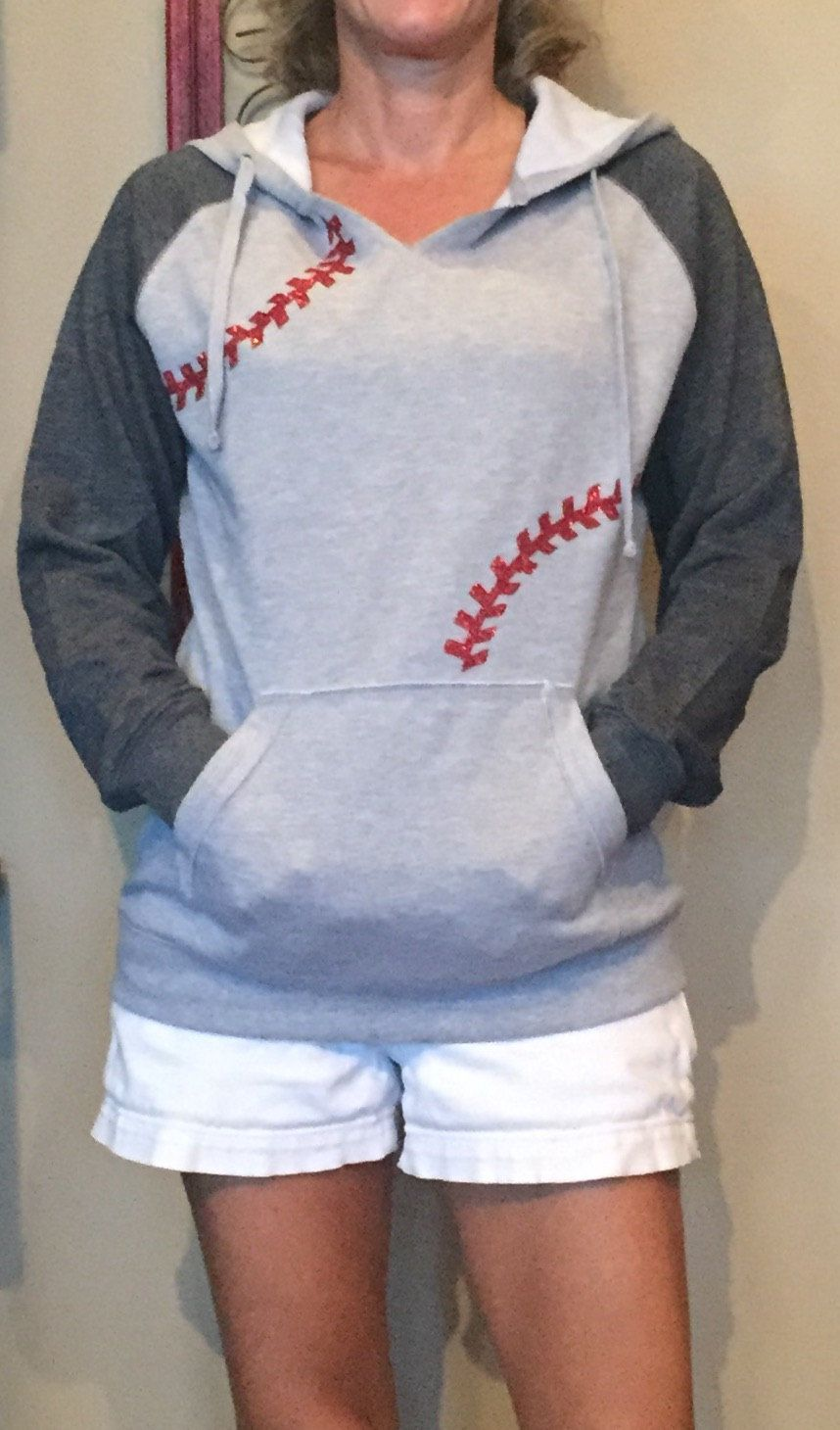 Baseball Seams Hooded Raglan Fleece Sweatshirt, super comfy and warm for early spring ball, features red glitter baseball seams.  Bright colorblocking on the hood and sleeves adds sporty appeal, while the 2x2 rib knit details make it modern. Colorfastness and minimal shrinkage means this soft sweatshirt will keep its great look and fit.  9-ounce, 65/35 ring spun combed cotton/poly fleece Three-panel hood Dyed-to-match drawcords Twill-taped neck Rib knit V patch at neck 2x2 rib knit ...