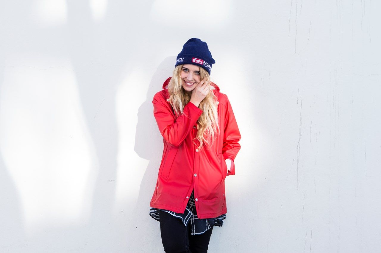 Salka Sól - 66°NORTH red pvc raincoat girl great smile 66north Salka Sól wearing Laugavegur women's rainjacket. Photograph: Gunnar Sverrisson
